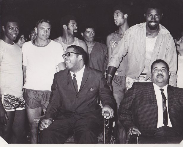 Stokes (left) and Roy Campanella (right) became friends following accidents less than two months apart in early 1958 that left both sports stars paralyzed.  Campanella was a three-time National League Most Valuable Player as a catcher with the Brooklyn Dodgers.  He and Maurice are seen here at one of the Stokes Benefit Games at Kutsher's Resort.  In the back row, left to right, are NBA stars Oscar Robertson, Dave DeBusschere, Gus Johnson, Wes Unseld, Kareem Abdul-Jabbar and Wilt Chamberlain (Saint Francis University Marketing and Public Relations).